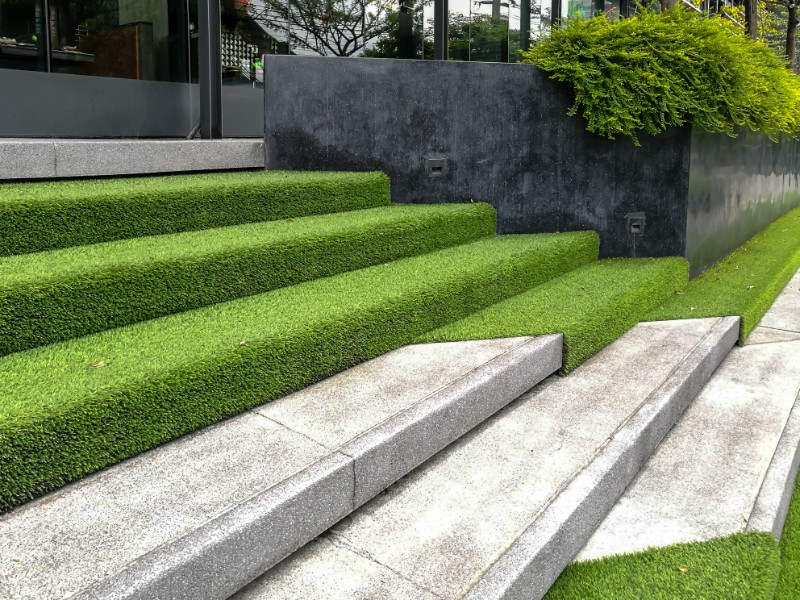 artificial grass being laid on outdoor stairs