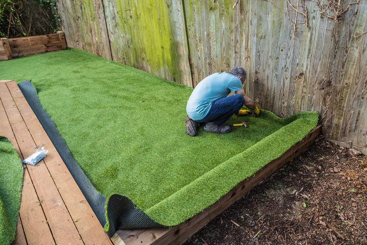 man installing artificial grass on decking